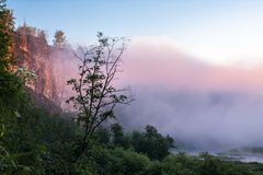 Foggy sunrise on the mountain river. Colorful fog near the river in the morning Stock Images