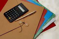 Colorful folders, calculator and gold pen Royalty Free Stock Images
