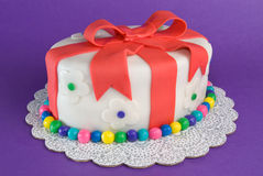 Colorful Fondant Gift Cake. A fondant-covered cake in the shape of a gift sits on purple Stock Photo