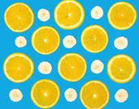 Colorful food fruit pattern of fresh orange and banana slices on bright blue background, top view, color wallpaper Stock Image