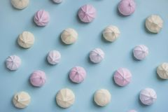 Colorful food pattern of pink, yellow and white meringues on blue background. stock photography