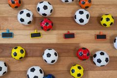 Colorful footballs on wooden table Royalty Free Stock Image