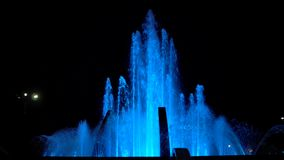 Colorful streams of water in fountain at night time, super slow motion. Colorful fountain with bright illumination against the black sky background at the stock video