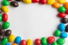 Colorful frame of multicolored candies on white background. Multicolor chocolate candies on the white background stock photos