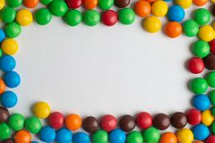 Colorful frame of multicolored candies on white background. Multicolor chocolate candies on the white background royalty free stock photography