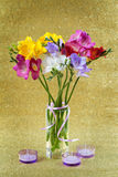 Colorful of freesia in vase and candles Stock Photos