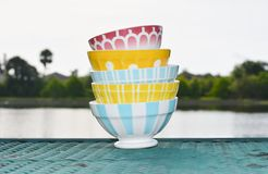 Colorful French Cafe au Lait Bowls. Colorful Vintage French Cafe au Lait  bowls in assorted patterns with water background Royalty Free Stock Photo