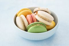 Colorful french macarons in a bowl on blue background. Colorful french macarons with different fillings in a bowl on blue background royalty free stock image