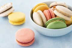 Colorful french macarons in a bowl on blue background. Colorful french macarons with different fillings in a bowl on blue background stock image