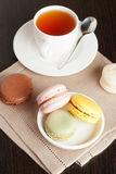 Colorful French Macaroon with Cup of Tea on black background. Vertical Stock Photos
