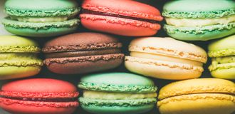 Colorful French macaroons cookies stacked in rows, wide composition royalty free stock photos