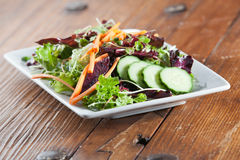 Colorful fresh arugula salad on rustic wooden table Stock Photos