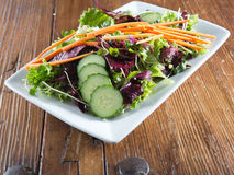 Colorful fresh arugula salad on rustic wooden table Royalty Free Stock Photos
