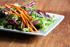 Colorful fresh arugula salad on rustic wooden table Stock Photography