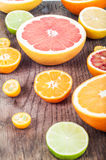 Colorful fresh citrus fruit on wooden background. Orange, tanger Stock Image