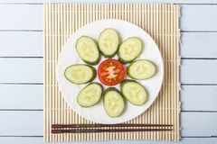 Colorful fresh dietary snack from natural vegetables on white plate. Sliced red tomato, cucumber in form of flower and chopsticks. Wooden table and bamboo mat Stock Photo