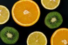 Colorful fresh fruits on a dark background. Orange, mandarin, kiwi, lemon. Fruit background. Summer food concept stock image