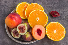 Colorful fresh fruits - figs, oranges and peaches on a dark back Stock Image