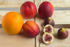 Colorful fresh fruits - oranges, figs and peaches lie on a woode Stock Images