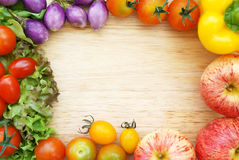 Colorful fresh organic vegetables composing a frame on a wooden chopping board. royalty free stock image