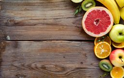 Colorful fresh summer fruits on brown wooden background, healthy food, top view royalty free stock image