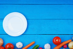 Colorful fresh vegetables and white plate on table. Colorful fresh vegetables and white plate on blue table Stock Images