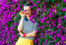 Happy woman near colorful magenta flowers bed having fun time. Colorful Freshness. happy stylish woman in yellow shorts and stripy shirt near colorful magenta Royalty Free Stock Images