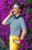 Smiling trendy woman near flowers bed speaking on cell phone Royalty Free Stock Photo