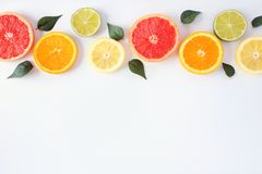 Colorful fruit border of fresh citrus slices with leaves. Top view, flay lay over a white background with copy space. Colorful fruit border of fresh citrus stock image