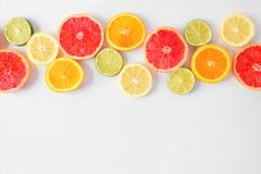 Colorful fruit border of citrus slices, top view over a white background. Colorful fruit border of fresh citrus slices. Top view, flat lay over a white royalty free stock photo