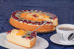 Colorful fruit cake with a cover charge of cup and plate. On blue tablecloth Stock Photos