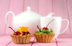 Colorful fruit cakes made with kiwi, orange, candied cherries and chocolate on a pink background with a teapot and cup royalty free stock photo