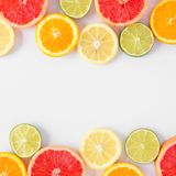 Colorful fruit square double border of citrus slices, top view over a white background. Colorful fruit double border of fresh citrus slices. Top view, flat lay royalty free stock images