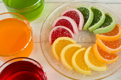Colorful fruit jelly candies arranged in circle on wooden table. Royalty Free Stock Images