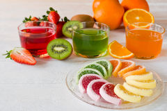Colorful fruit jelly candies arranged in circle on wooden table. Stock Photos