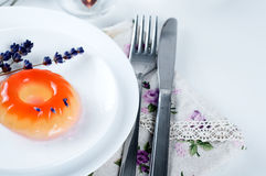 Colorful fruit jelly sweets on a white plate. With lavander and tea Stock Image