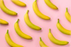 Colorful fruit pattern. Bananas over pink background. Top view. Pop art design, creative summer concept. Minimal flat lay style. Colorful fruit pattern. Bananas stock image
