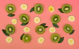 Colorful fruit pattern of fresh kiwi and banana slices on pink background royalty free stock image
