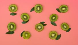 Colorful fruit pattern of fresh kiwi slices on pink background stock photography