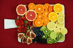 Colorful fruit platter assembly with rainbow color fruit pieces including citrus, berries, figs, and kiwi fruit. royalty free stock photo
