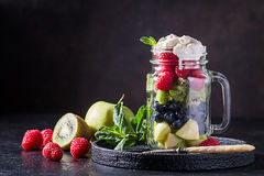 Colorful fruit salad. With cream in a jar on black background Stock Photo