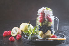 Colorful fruit salad. With cream in a jar on black background Stock Photos