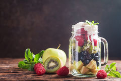 Colorful fruit salad. With cream in a jar on wooden background Stock Image