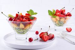 Colorful fruit salad in the glass bowl. Strawberries, kiwis and apricots dessert. Colorful fruit salad in the glass bowl. Strawberries, kiwis and apricots stock images