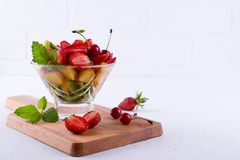 Colorful fruit salad in the glass bowl. Strawberries, kiwis and apricots dessert stock photography