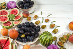 Colorful fruit set of purple, red and orange background in bowls. Plum, peaches, watermelon sliced above white tabletop Royalty Free Stock Photography