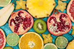Colorful fruit slices on blue wood surface Royalty Free Stock Image