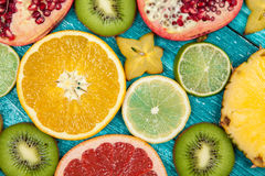 Colorful fruit slices on blue wood surface Royalty Free Stock Photos