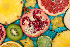 Colorful fruit slices on blue wood surface Royalty Free Stock Images