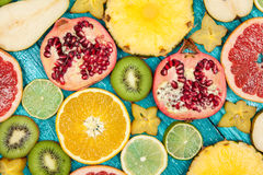 Colorful fruit slices on blue wood surface Stock Photo